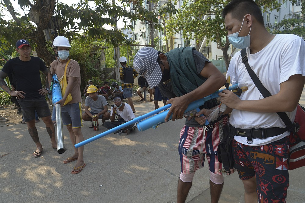 """Anti-coup protesters check their homemade air guns in Yangon, Myanmar on Thursday, March 24, 2021. Protesters against last month's military takeover in Myanmar returned to the streets in large numbers Thursday, a day after staging a """"silence strike"""" in which people were urged to stay home and businesses to close for the day. (AP Photo)"""