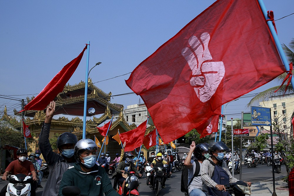 """Engineers carry flags bearing the three-fingers salute as they drive their motorcycles during an anti-coup protest in Mandalay, Myanmar on Thursday March 25, 2021. Protesters against last month's military takeover in Myanmar returned to the streets in large numbers Thursday, a day after staging a """"silence strike"""" in which people were urged to stay home and businesses to close for the day. (AP Photo)"""