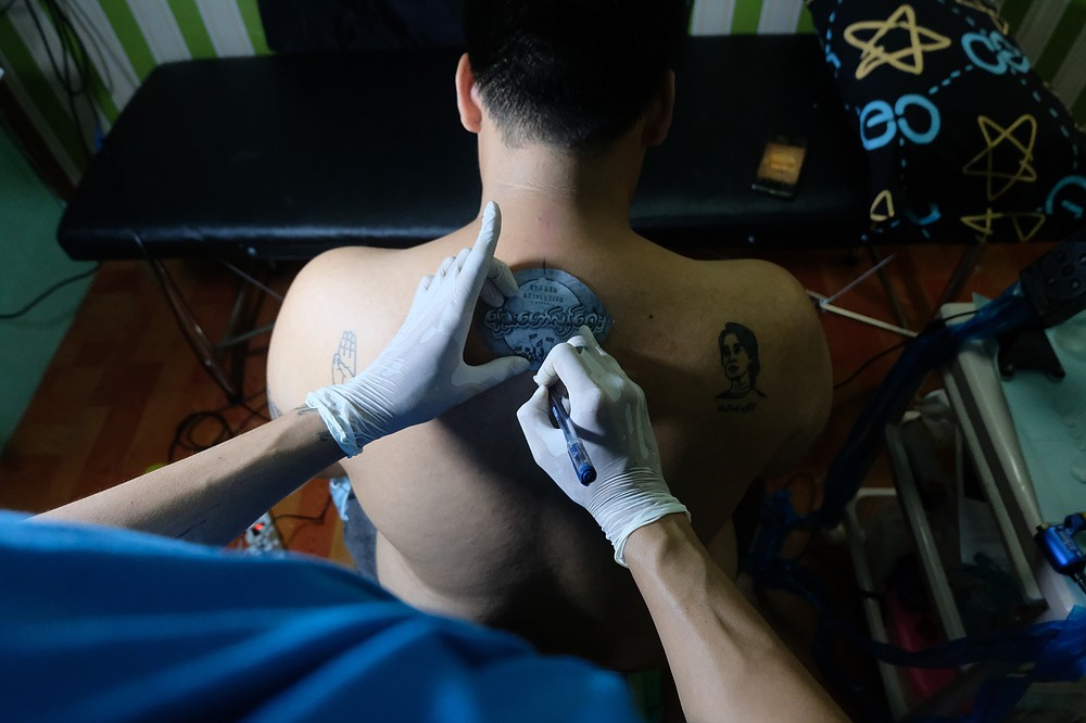 """A tattoo artist outlines a design with Burmese text that reads """"spring revolution"""" on the back of a man with other tattoos that depict the anti-coup three-fingered protest salute and deposed Myanmar leader Aung San Suu Kyi in Yangon, Myanmar Thursday, Mar. 25, 2021. (AP Photo)"""