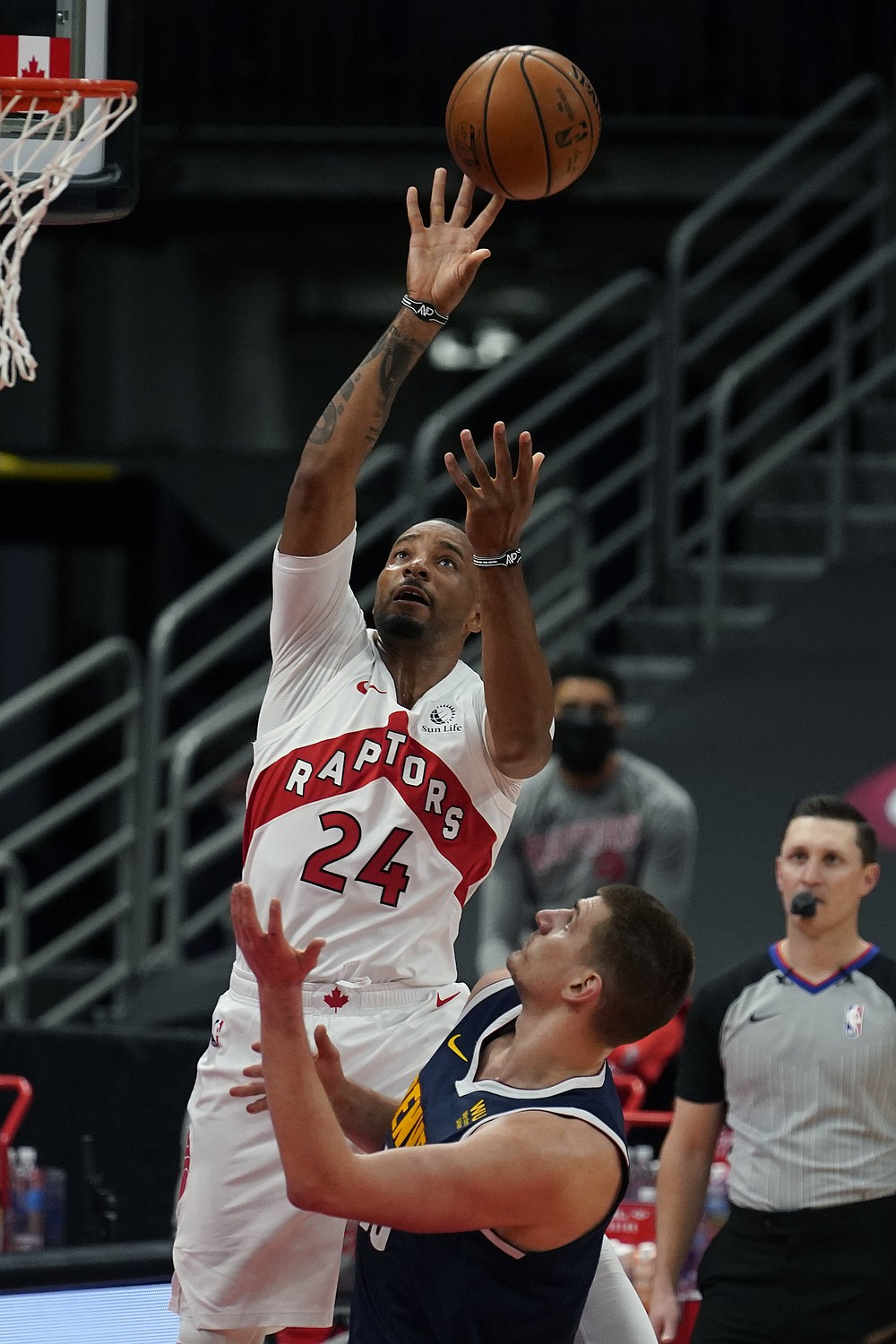 Toronto Raptors forward Norman Powell (24) grabs a rebound over Denver Nuggets center Nikola Jokic (15) during the first half of an NBA basketball game Wednesday, March 24, 2021, in Tampa, Fla. (AP Photo/Chris O'Meara)