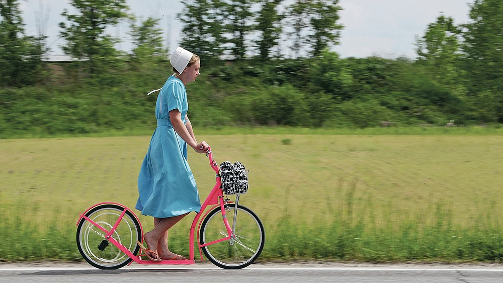 An Amish girl rides her scooter, Wednesday, May 27, 2020, near Middlefield, Ohio. (AP Photo/Tony Dejak)