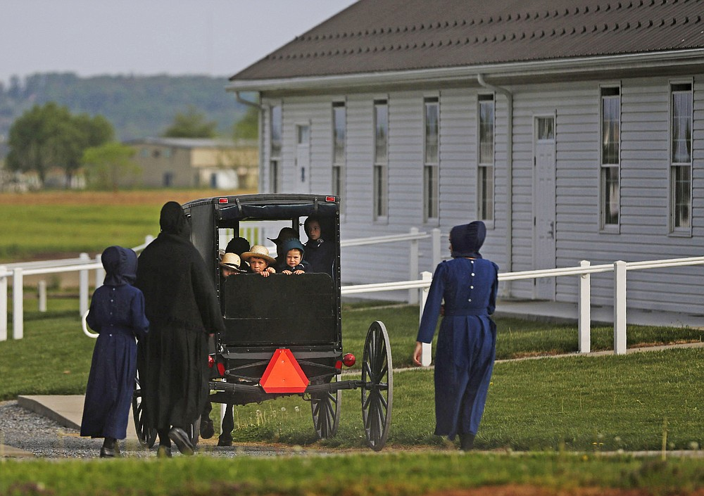 In this Sunday, May 17, 2020, photo, families of the Old Order Stauffer Mennonite Church in New Holland, Pa., arrive by horse-drawn buggy for their first in-person church service in nearly two months due to the coronavirus. (AP Photo/Jessie Wardarski)