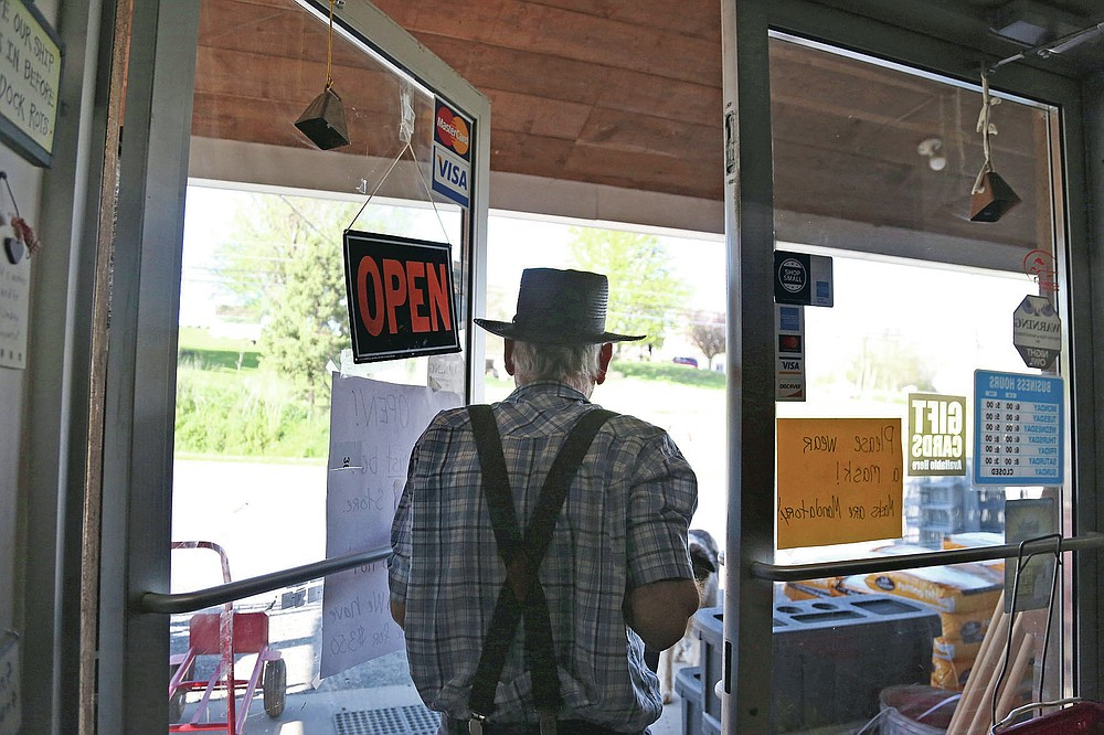 In this Monday, May 4, 2020, photo, Aaron Hurst, owner of AAA Farm Supply and member of the Old Order Groffdale Conference Mennonite Church closes his business for the day in Terre Hill, Pa. Hurst kept his hardware and animal food supply store open through the coronavirus outbreak by taking precautions such as porch pick-up service and mandatory masks. (AP Photo/Jessie Wardarski)