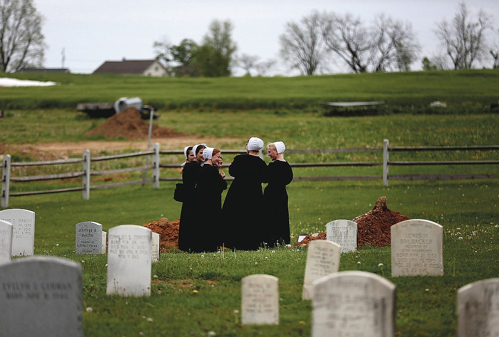 In this Sunday, May 17, 2020, photo, a group of friends visit the grave of a fellow Old Order Stauffer Mennonite member in a cemetery next to the church in New Holland, Pa. The women were among dozens of other congregants who attended the church's first in-person service since the start of the coronavirus outbreak in March. (AP Photo/Jessie Wardarski)
