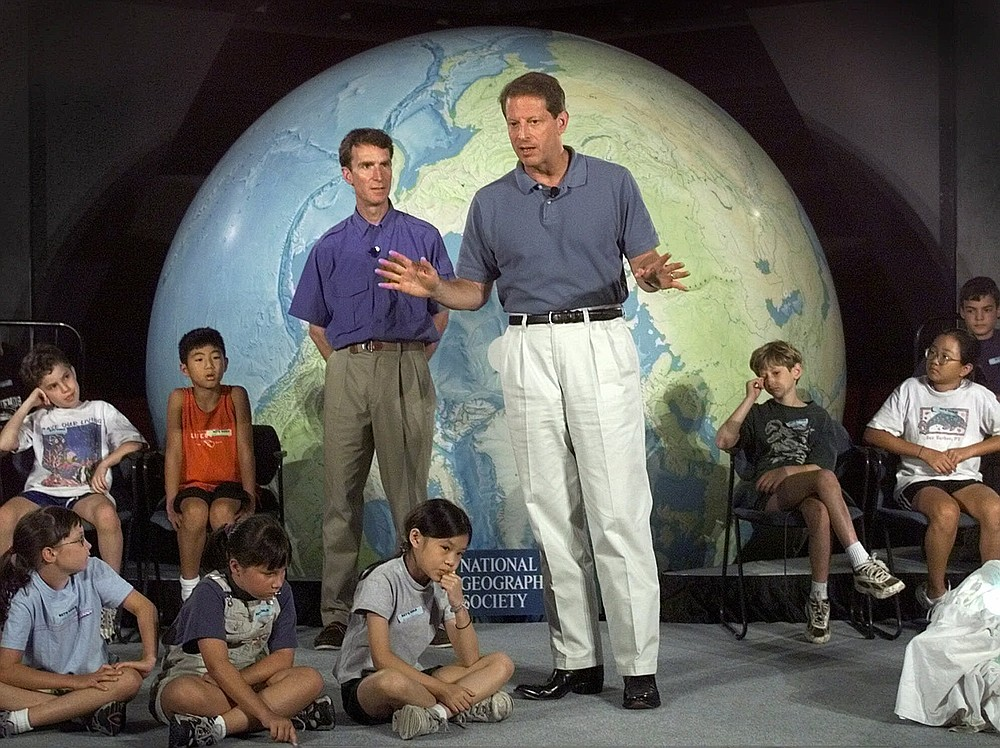 """FILE - In this Aug. 2, 1999, file photo Vice President Al Gore, accompanied by Bill Nye """"The Science Guy"""" gestures while talking about climate change to summer camp students at the National Geographic Society in Washington. (AP Photo/Khue Bui, File)"""