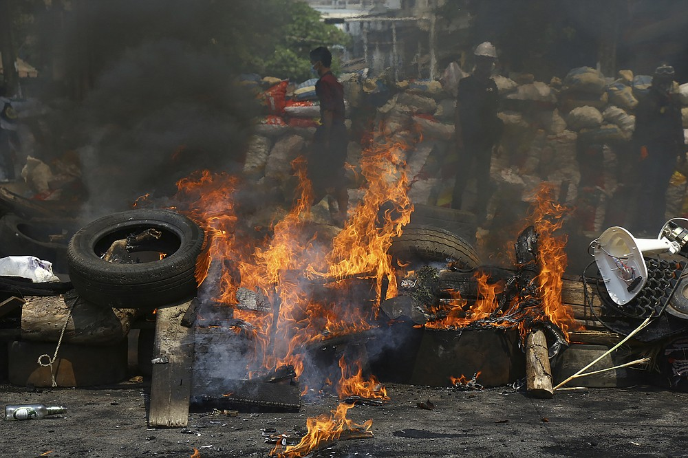 Anti-coup protesters are seen behind their makeshift barricade that protesters burn to make defense line during a demonstration in Yangon, Myanmar, Sunday, March 28, 2021. Protesters in Myanmar returned to the streets Sunday to press their demands for a return to democracy, just a day after security forces killed more than 100 people in the bloodiest day since last month's military coup. (AP Photo)