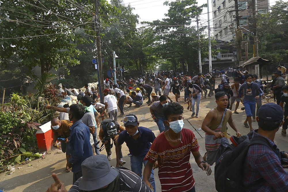 Anti-coup protesters disperse as the protesters confront police in Yangon, Myanmar Sunday, March 28, 2021. Protesters in Myanmar returned to the streets Sunday to press their demands for a return to democracy, just a day after security forces killed more than 100 people in the bloodiest day since last month's military coup. (AP Photo)