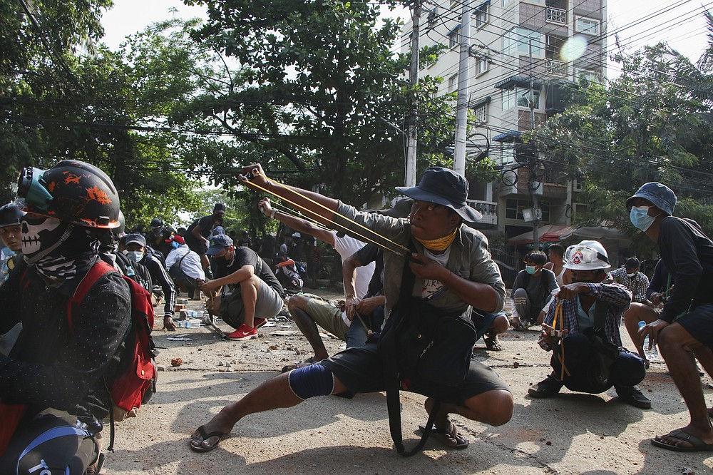 Anti-coup protesters use sling shot to confront police at Thaketa Township in Yangon, Myanmar, Sunday, March 28, 2021. Protesters in Myanmar returned to the streets Sunday to press their demands for a return to democracy, just a day after security forces killed more than 100 people in the bloodiest day since last month's military coup. (AP Photo)