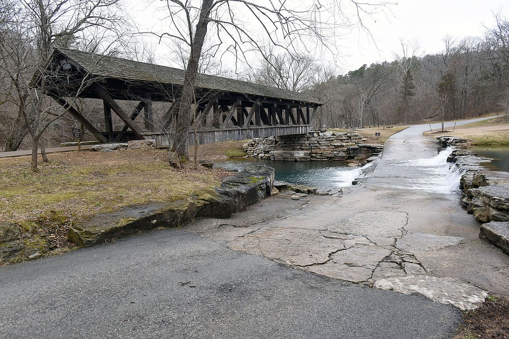 Hikers and bicycle riders cross a covered bridge. (NWA Democrat-Gazette/Flip Putthoff)