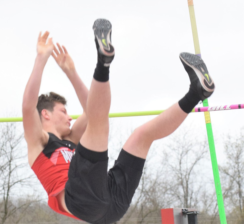 RICK PECK/SPECIAL TO MCDONALD COUNTY PRESS McDonald County's Andrew Watkins clears the bar on the way to a third place finish in the pole vault at the Stancell McDonald County Stampede held on March 25, at McDonald County High School.