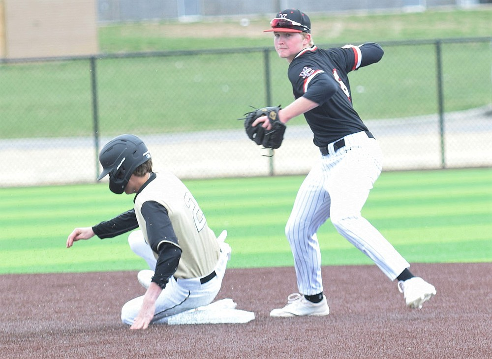 RICK PECK/SPECIAL TO MCDONALD COUNTY PRESS McDonald County second baseman Levi Helm forces out a Neosho runner before throwing to first to complete a double play in the Mustangs' 5-3 win over Neosho on March 23 at Neosho High School.