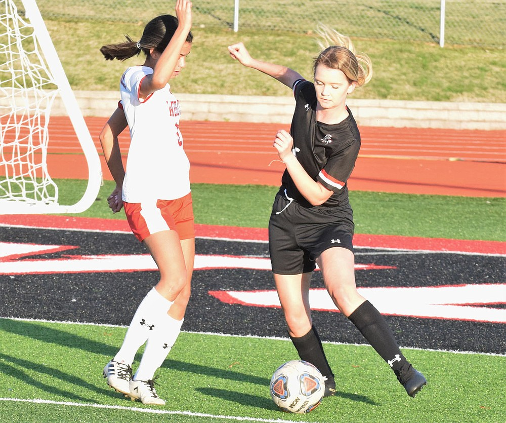 RICK PECK/SPECIAL TO MCDONALD COUNTY PRESS McDonald County defender Faith Leach tries to clear the ball from the Lady Mustang zone during Webb City's 8-0 win on March 26 at McDonald County High School.