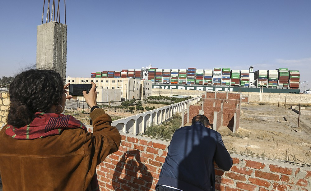 People watch Ever Given, a Panama-flagged cargo ship, that has been stuck sideways and blocked traffic in Egypt's Suez Canal, move past after it was set free by salvage teams, Monday, March 29, 2021. (AP Photo/Mohamed Elshahed)