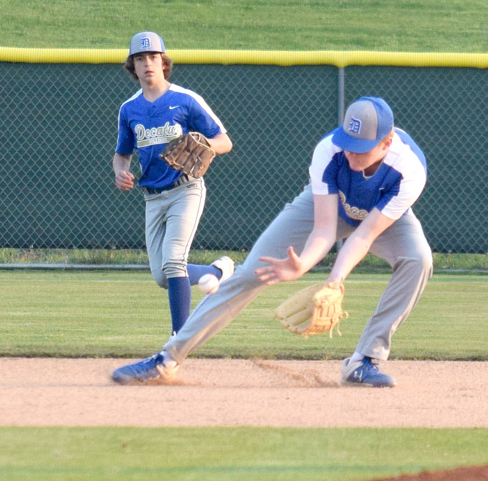 Westside Eagle Observer/MIKE ECKELS  Bryson Funk (right) scoops up a ground ball hit into center field during the Thaden-Decatur variety baseball contest at the Tyson Baseball Complex in Springdale March 29. The Bulldogs lost to the Barnstormers 5-2 in a non-conference contest.