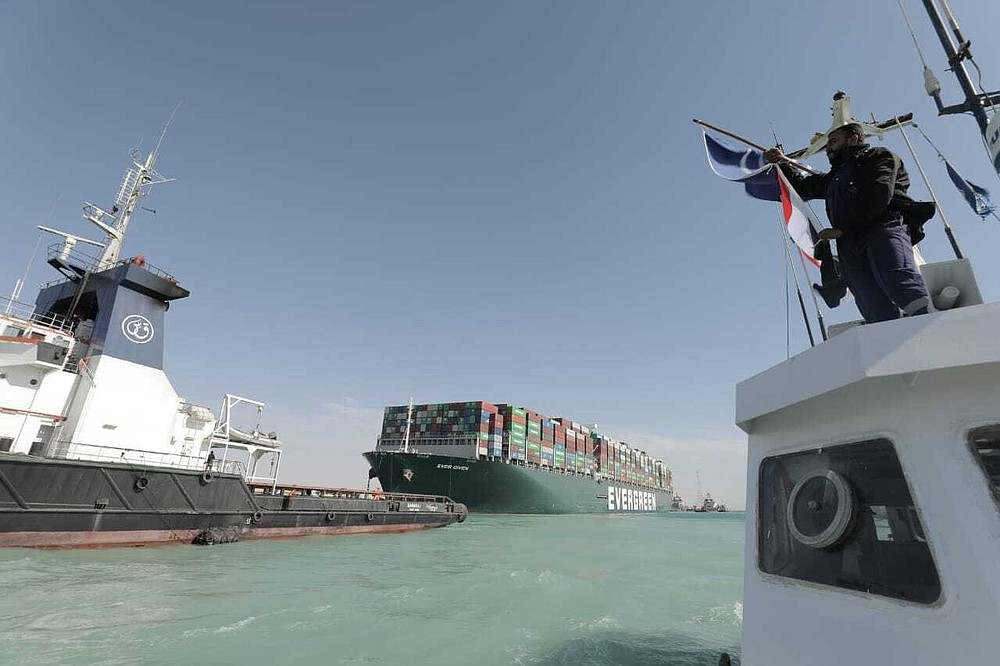 In this photo released by Suez Canal Authority, the Ever Given, a Panama-flagged cargo ship is accompanied by Suez Canal tugboats as it moves in the Suez Canal, Egypt, Monday, March 29, 2021. Salvage teams on Monday set free a colossal container ship that has halted global trade through the Suez Canal, bringing an end to a crisis that for nearly a week had clogged one of the world's most vital maritime arteries. (Suez Canal Authority via AP)