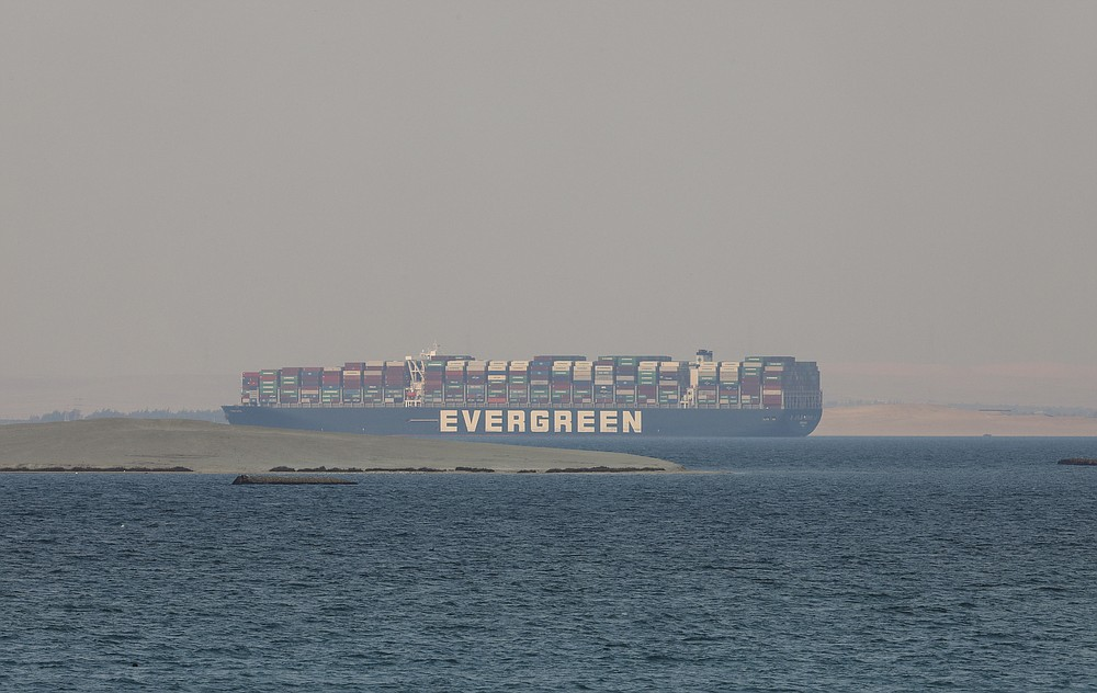 Ever Given, a Panama-flagged cargo ship, is seen in Egypt's Great Bitter Lake Tuesday, March 30, 2021. Experts have boarded Ever Given container ship that had blocked the Suez Canal for nearly a week before it was dislodged. A canal pilot says engineers are inspecting the Ever Given for damage and trying to determine why it ran aground. (AP Photo/Mohamed Elshahed)