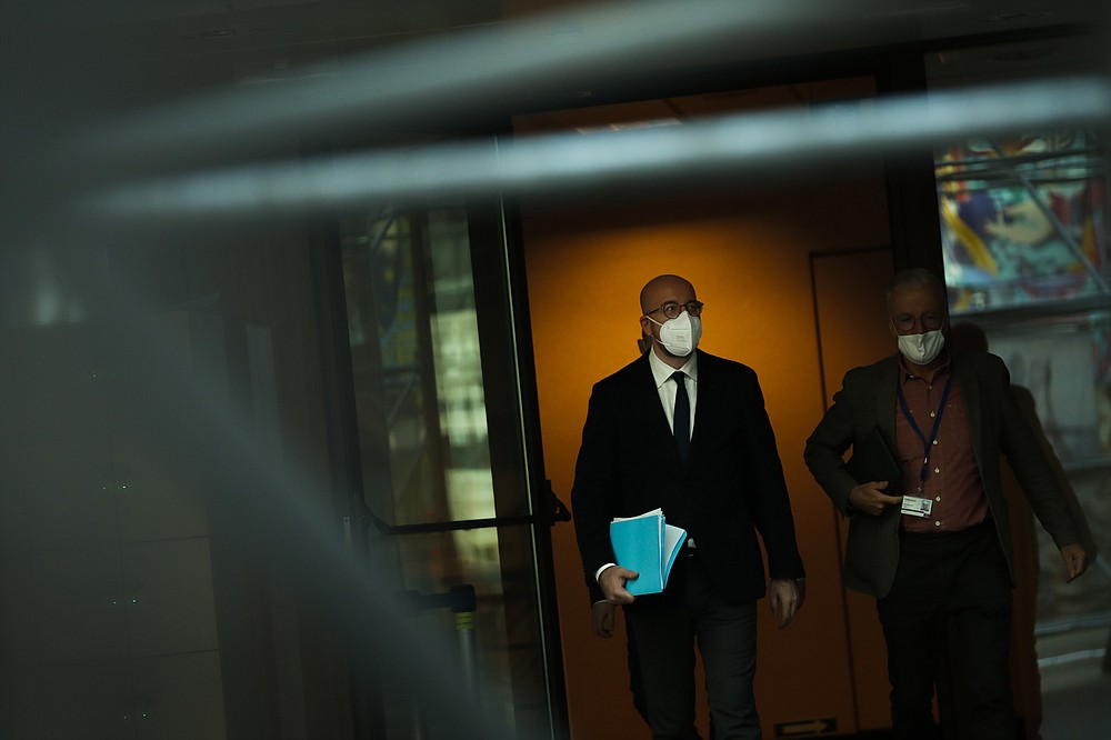 European Council President Charles Michel, left, leaves after an online joint press conference with Director General of the World Health Organization Tedros Adhanom Ghebreyesus at the European Council headquarters in Brussels, Tuesday, March 30, 2021. (AP Photo/Francisco Seco, Pool)