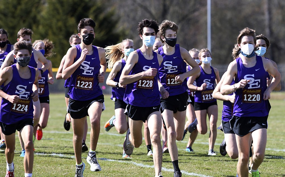 Runners from South Eugene join a cross-country meet at Marist High School in Eugene, Ore., on March 13, 2021. Oregon has one of the country's strictest mask requirements. Even high school athletes must wear them while running races. (Chris Pietsch/The Register-Guard via AP)