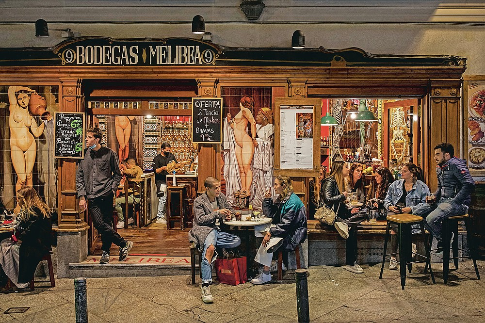 Tourists and locals have drinks at a bar in downtown Madrid, Spain, Friday, March 26, 2021. With its policy of open bars and restaurants, Madrid has built itself a reputation of something like Europe's last reduct for fun. That's driving some business to locals and giving politicians and the media much to debate about ahead of a regional election. (AP Photo/Bernat Armangue)
