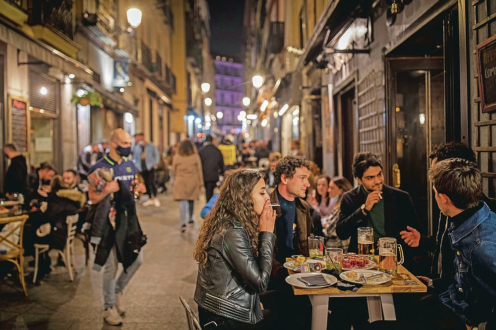 Tourists and locals have drinks at a bar in downtown Madrid, Spain, Friday, March 26, 2021. With its policy of open bars and restaurants — indoors and outdoors — and by keeping museums and theaters running even when outbreaks have strained hospitals, Madrid has built a reputation as an oasis of fun in Europe's desert of restrictions. Other Spanish regions have a stricter approach to entertainment. Even sunny coastal resorts offer a limited range of options for the few visitors that started to arrive, coinciding with Easter week, amid a set of contradictory European travel rules. (AP Photo/Bernat Armangue)