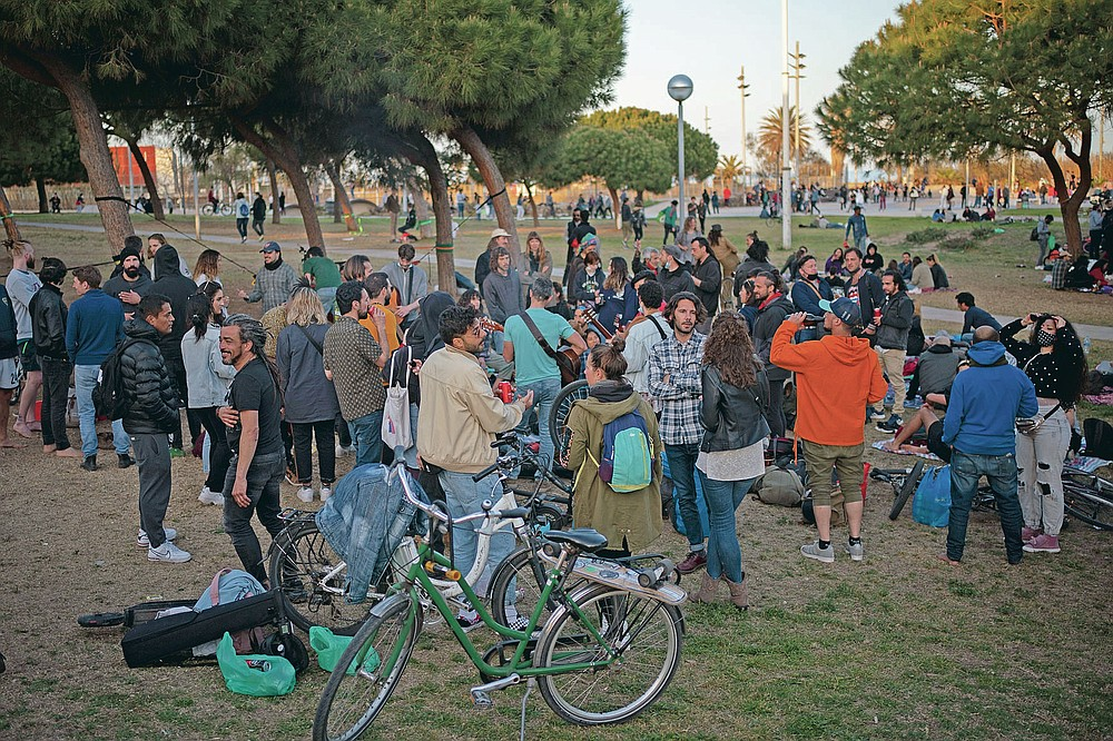 Local people gather at a public park in Barcelona, Spain, Sunday, March 28, 2021. Efforts in Spain to restart tourism activity is drawing a mixed picture due to a patchwork of national, regional and European rules on travel that is confusing both tourists and their hosts. (AP Photo/Emilio Morenatti)