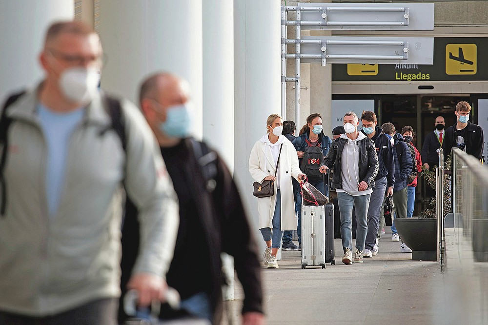 Passengers wearing face masks arrive at Palma de Mallorca Airport on the Spanish Balearic Island of Mallorca, Spain, Saturday, March 27, 2021. Efforts in Spain to restart tourism activity is drawing a mixed picture due to a patchwork of national, regional and European rules on travel that is confusing both tourists and their hosts. (AP Photo/Francisco Ubilla)