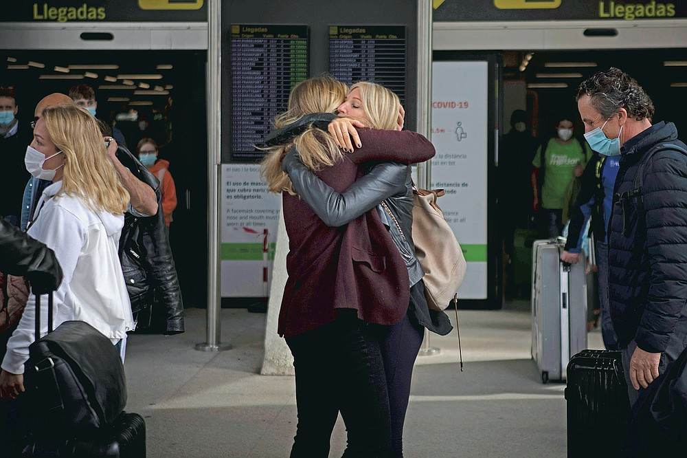 Two women meet at Palma de Mallorca Airport on the Spanish Balearic Island of Mallorca, Spain, Saturday, March 27, 2021. Efforts in Spain to restart tourism activity is drawing a mixed picture due to a patchwork of national, regional and European rules on travel that is confusing both tourists and their hosts. (AP Photo/Francisco Ubilla)