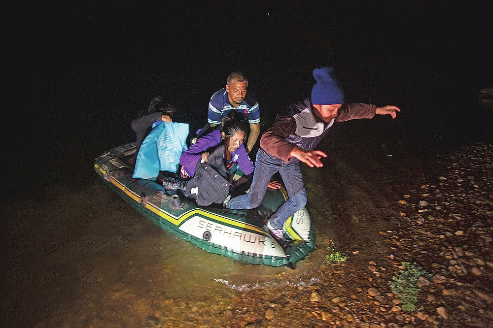 Migrant families, mostly from Central American countries, wade through shallow waters after being delivered by smugglers on small inflatable rafts on U.S. soil in Roma, Texas, Wednesday, March 24, 2021. (AP Photo/Dario Lopez-Mills)