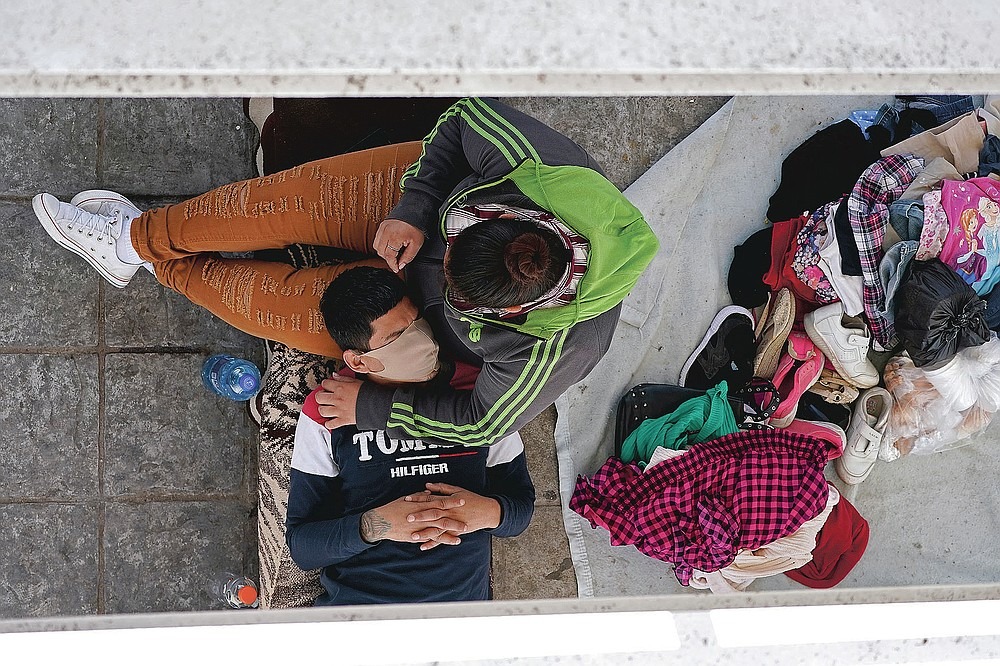 Migrants who were caught trying to cross into the U.S. and were deported rest under a ramp that leads to the McAllen-Hidalgo International Bridge on Thursday, March 18, 2021, in Reynosa, Mexico. (AP Photo/Julio Cortez)