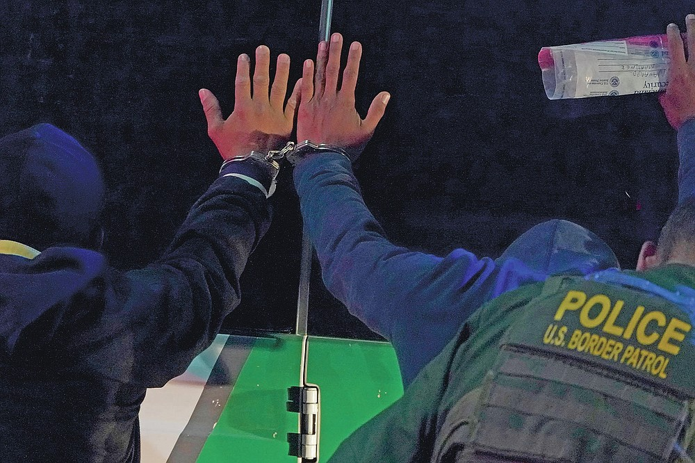 Two men are handcuffed together as a U.S. Customs and Border Protection agent pats them down before putting them in a van while taking them into custody near the U.S.-Mexico border, Saturday, March 20, 2021, in Hidalgo, Texas. (AP Photo/Julio Cortez)