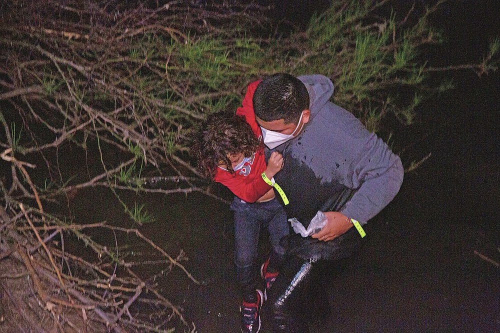 A father helps her daughter after they were smuggled on an inflatable raft across the Rio Grande, in Roma, Texas Saturday, March 27, 2021. (AP Photo/Dario Lopez-Mills)