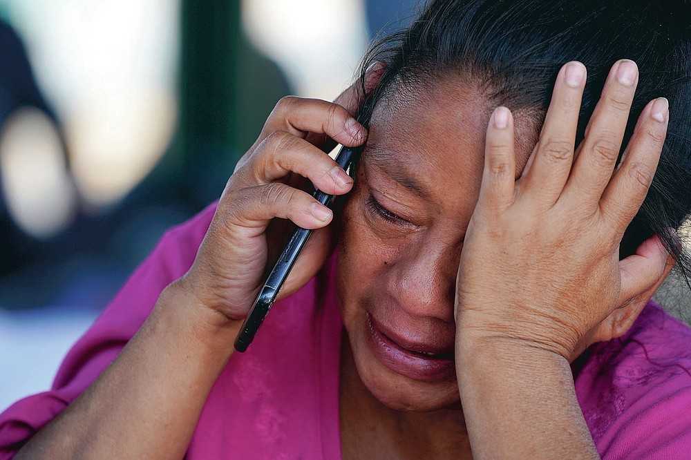 A migrant woman cries as she talks on a cellphone at a park after she and a large group of deportees from the U.S. were pushed by Mexican authorities off an area they had been staying after their expulsion, Saturday, March 20, 2021, in Reynosa, Mexico. (AP Photo/Julio Cortez)
