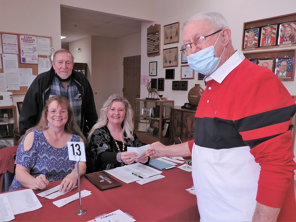 From left, seated at table, are Jackie Brown and Ginger Yates, president of Emblem Club No. 194, Gaylord Brown, standing behind registration table, and Herb Carey, PER, PDDGER, in front of the table. - Submitted photo