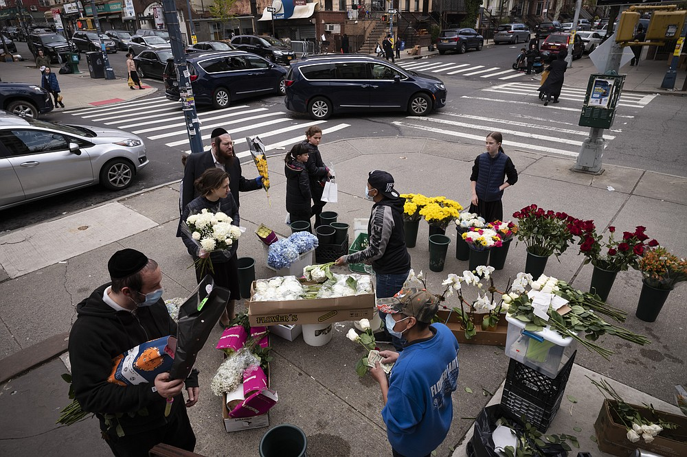 FILE - In this Wednesday, April 8, 2020 file photo, people buy flowers from a sidewalk flower stand on the first day of Passover in the Williamsburg neighborhood of New York during the coronavirus pandemic. (AP Photo/Mark Lennihan)