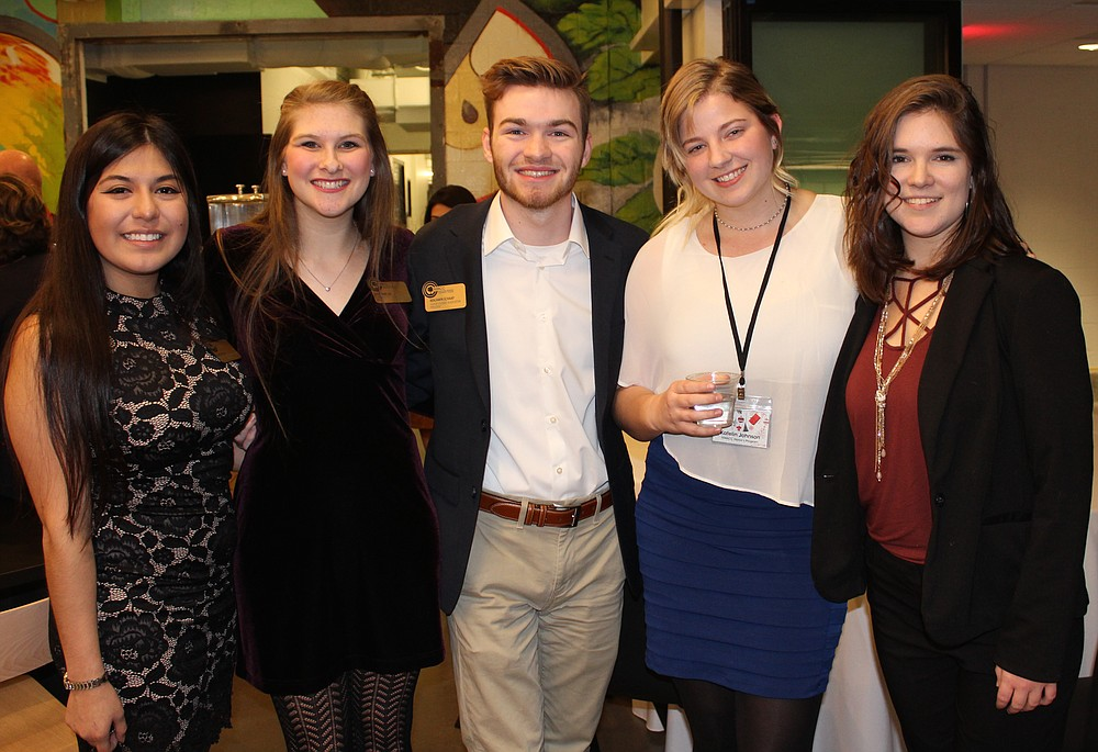 NWA Democrat-Gazette/CARIN SCHOPPMEYER Llanet Sanchez (from left), Katherine Leis, Benjamin Schaap, Katelin Johnson and Megan Butler, Northwest Arkansas Community College students, help welcome guests to the college's holiday reception Dec. 12 at Brightwater in Bentonville.
