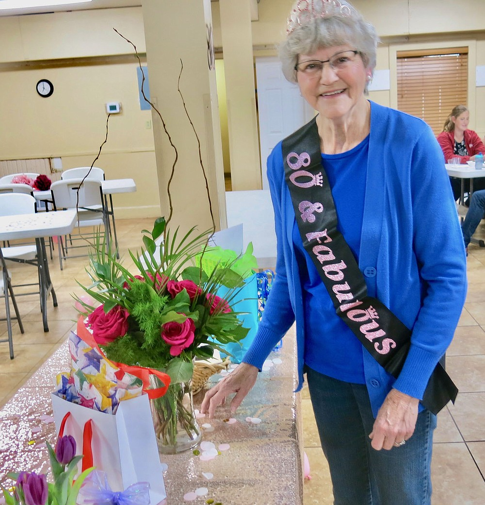 """Westside Eagle Observer/SUSAN HOLLAND Jeanie Easley, of Gravette, poses with a lovely bouquet of red roses as she looks over a table full of gifts and cards at her 80th birthday party Wednesday evening, March 31, at the First Baptist Church. Jeanie's daughter and son-in-law, Carla and David Bailey, surprised her with a party when she thought she was just going out to eat for the evening. They took her by the church where she was fitted with a tiara and sash announcing she was """"80 and Fabulous"""" and found a full-fledged party with snacks, drinks, birthday cake and a roomful of friends to help her celebrate."""