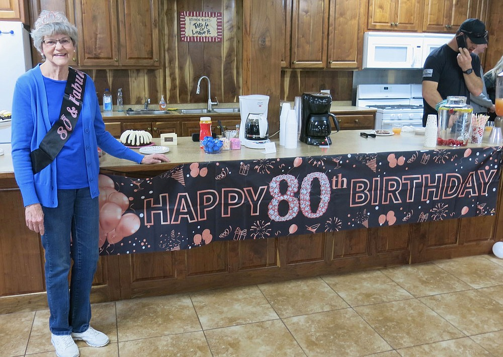 """Westside Eagle Observer/SUSAN HOLLAND Jeanie Easley, of Gravette, shows off the banner wishing her a """"Happy 80th Birthday"""" Wednesday evening, March 13, at the First Baptist Church. Easley was treated to a surprise 80th birthday party by her daughter and son-in-law, Carla and David Bailey, who invited her out to eat for the evening. Several friends and family members came out to help her celebrate with snacks and drinks, birthday cake, gifts and cards."""
