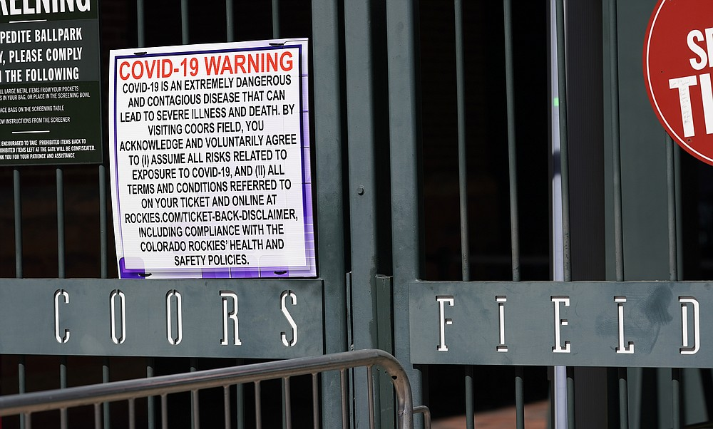 Signs hang on the first-base gates of Coors Field as one of the steps to stop the spread of the coronavirus as fans return for the first inning of a baseball game between the Los Angeles Dodgers and the Colorado Rockies Thursday, April 1, 2021, in Denver. (AP Photo/David Zalubowski)