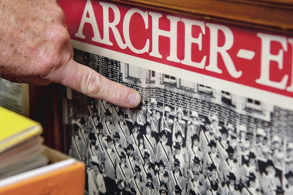 Bill Ives points to himself in a 1981 photo with the Archer-Epler Musketeers Drum and Bugle Corps, in Upper Darby, Pa., March 15, 2021. The marching band costumes, instruments, banners, flags, photos, programs, recordings, regalia, and memorabilia that Ives has assiduously amassed since 1990 — 24,000 pieces, and counting — are a showstopper. For now, they're stored or displayed at Upper Darby's venerable Archer-Epler VFW Post 979, the longtime headquarters of the Musketeers Drum and Bugle Corps. (Tom Gralish/The Philadelphia Inquirer via AP)