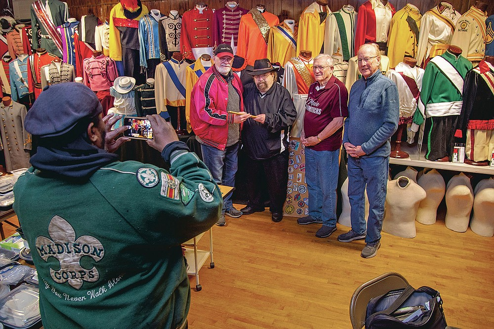 Wearing a jacket of the Madison Scouts Drum and Bugle Corps from Madison, Wis., Frederick Omega Pye, front left, takes a photo of a drum stick presentation at the Archer-Epler VFW Post 979 in Upper Darby, Pa., March 15, 2021. Bill Ives, left, posing was presented with the custom-made persimmon wood drumsticks crafted by John Crocken, second from right, who came up from Baltimore for the presentation. The sticks were purchased by Joe Marrella, second from left, who donated them to Ives. Eddie Gibson is at right. The post houses Ives' collection of over 24,000 marching band and drum and bugle corps memorabilia. (Tom Gralish/The Philadelphia Inquirer via AP)