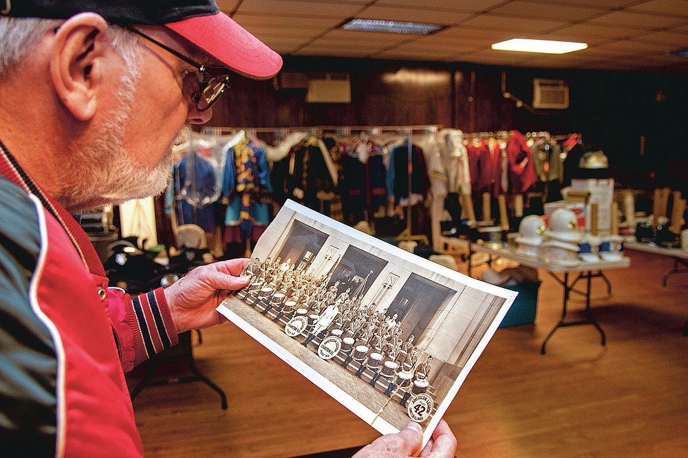 Bill Ives looks over marching band and drum and bugle corps memorabilia at the Archer-Epler VFW Post 979 in Upper Darby, Pa., March 15, 2021. This a photo of the 1933-34 champion Missouri Golden Troopers from American Legion Post 63 in Cape Girardeau, Mo. Marching band costumes, instruments, banners, flags, photos, programs, recordings, regalia, and memorabilia that Ives has assiduously amassed since 1990 — 24,000 pieces, and counting — are a showstopper. (Tom Gralish/The Philadelphia Inquirer via AP)