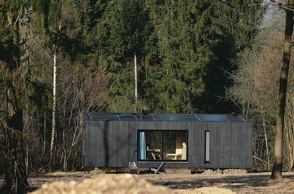 Solar panels on the roof generate energy for a Slow Cabin in Zandbergen, Belgium, Sunday, Feb. 28, 2021. These Slow Cabins, set up the Belgian countryside, are the new way to vacation in pandemic times: in complete solitude and in the middle of nowhere. The wooden cabins are fully sustainable, provided you don't stay in the shower too long and you can live without Wi-Fi. (AP Photo/Virginia Mayo)