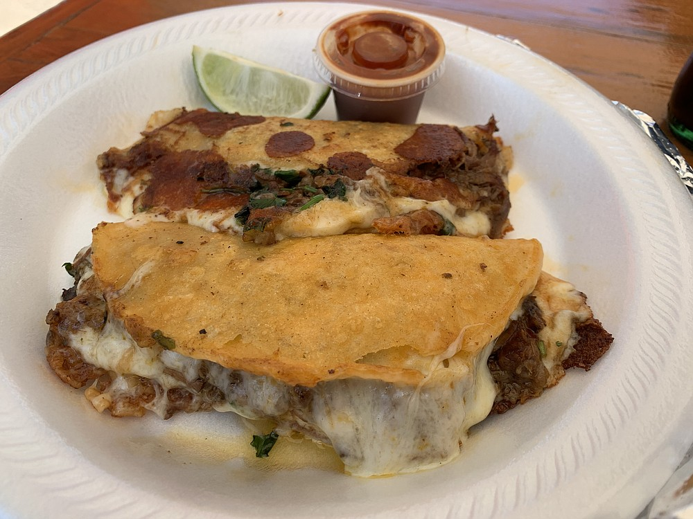 Our two press-fried Quesabirria tacos from the La Casa de mi Abuelita food truck were corn shells wrapping shredded beef and melted cheese. (Arkansas Democrat-Gazette/Eric E. Harrison)