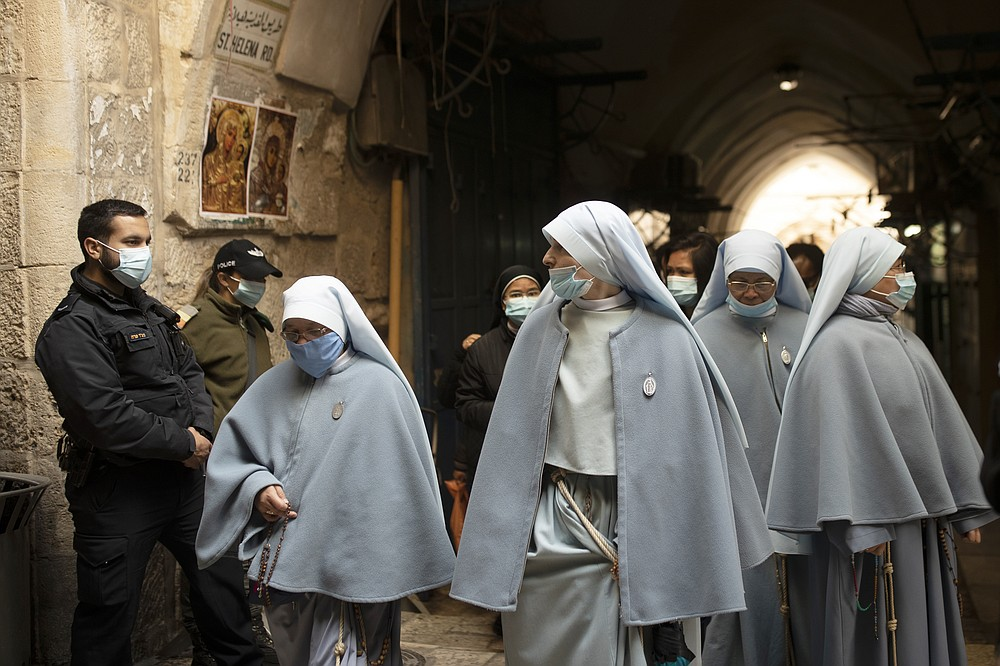 Nuns walk from the Church of the Holy Sepulchre, traditionally believed by many to be the site of the crucifixion of Jesus Christ, before the the Good Friday procession in Jerusalem's Old City, Friday, April 2, 2021. (AP Photo/Maya Alleruzzo)