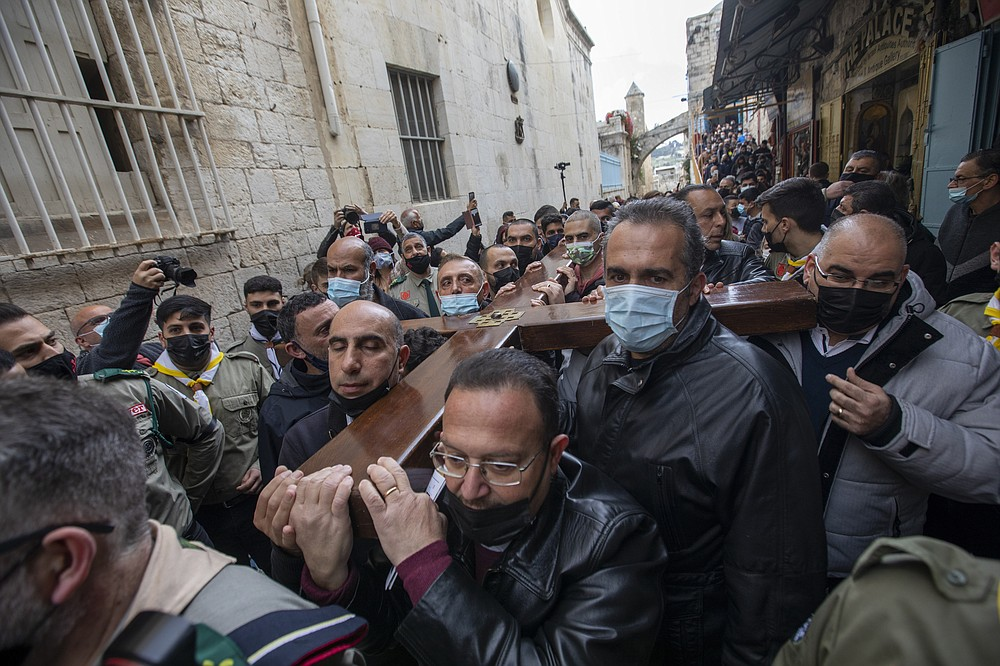 Christians carry a cross along the Via Dolorosa towards the Church of the Holy Sepulchre, traditionally believed by many to be the site of the crucifixion of Jesus Christ, during the Good Friday procession in Jerusalem's old city, Friday, April 2, 2021. (AP Photo/Ariel Schalit)