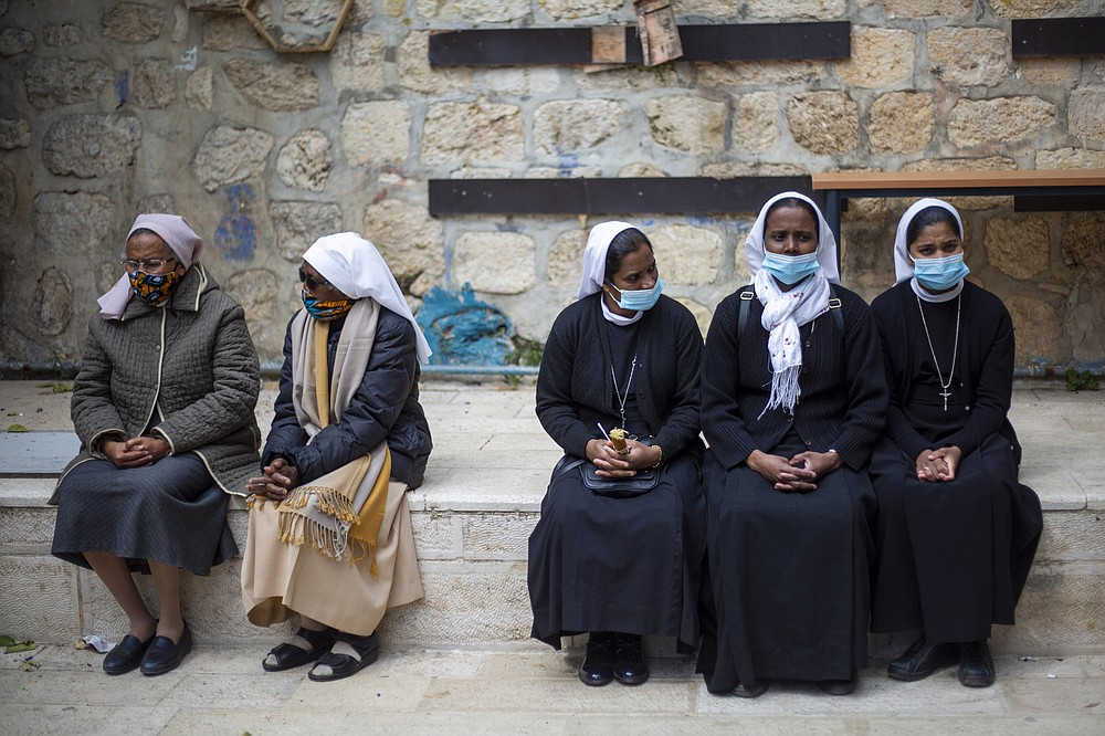 Nuns wait to the Good Friday procession along the Via Dolorosa near the Church of the Holy Sepulchre, traditionally believed by many to be the site of the crucifixion of Jesus Christ, during Jerusalem's old city, Friday, April 2, 2021. (AP Photo/Ariel Schalit)
