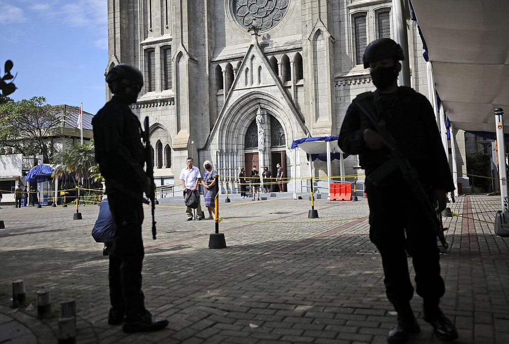 In the wake of suicide bomb attack at a church in Makassar, South Sulawesi on March 28, armed police stand guard outside the St. Mary of the Assumption Cathedral during Mass on the holy day of Good Friday, April 2, 2021, in Jakarta, Indonesia. (AP Photo/Dita Alangkara)