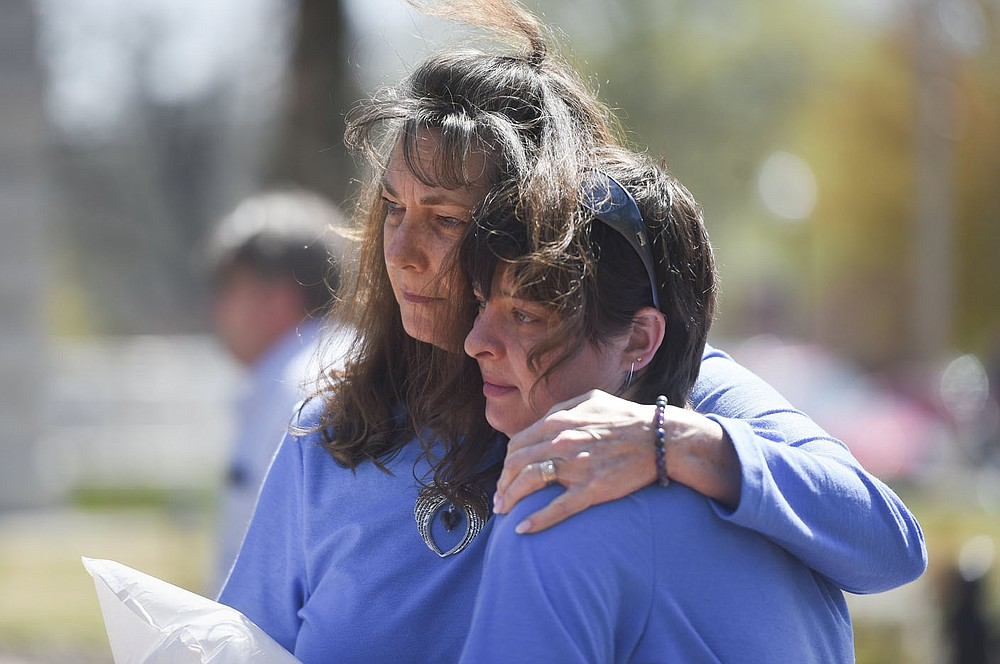 Vickie Price (from left) and DesaRae Crouch embrace, Friday, April 2, 2021 at the downtown square in Bentonville. The Children's Advocacy Center of Benton County Pinwheels for Prevention kicked off Child Abuse Awareness Month with speakers and an honorary dove release in remembrance of children lost to abuse in the community. Check out nwaonline.com/210403Daily/ for today's photo gallery.  (NWA Democrat-Gazette/Charlie Kaijo)