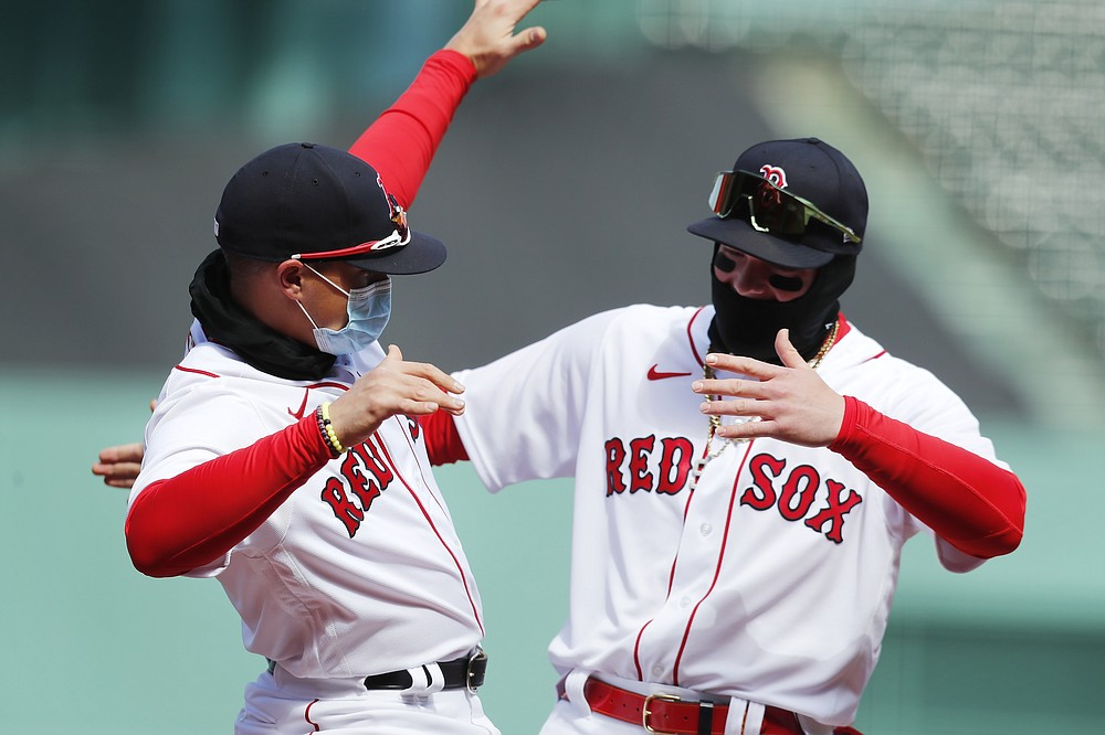 Boston Red Sox's Enrique Hernandez, left, and Alex Verdugo react during introductions before an opening day baseball game against the Baltimore Orioles, Friday, April 2, 2021, in Boston. (AP Photo/Michael Dwyer)