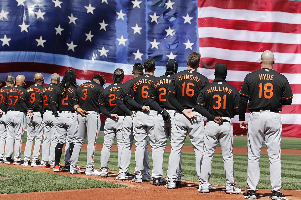 The Baltimore Orioles stand for the national anthem before an opening day baseball game against the Boston Red Sox, Friday, April 2, 2021, in Boston. (AP Photo/Michael Dwyer)